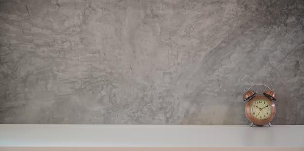 Area di lavoro del sottotetto con l'orologio dell'annata e lo spazio della copia con il fondo grigio della parete
