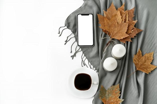 Area di lavoro della scrivania del ministero degli interni con il telefono cellulare con lo schermo bianco in bianco, tazza di caffè, taccuino su bianco