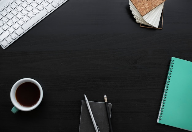 Area di lavoro della tazza di caffè delle matite del taccuino sulla tabella nera