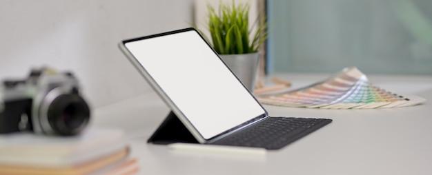 Area di lavoro di design con tablet, forniture di design, macchina fotografica e decorazione sul tavolo bianco