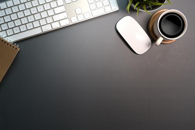 Area di lavoro di tavolo scrivania ufficio scuro con computer, forniture per ufficio e tazza di caffè.