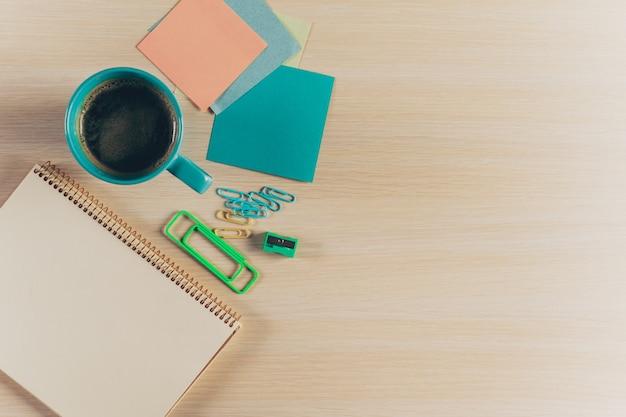 Area di lavoro di vista superiore con il taccuino e la penna in bianco sulla tavola di legno