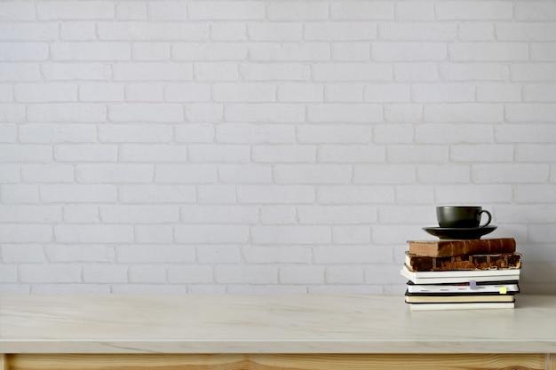 Area di lavoro e copia spazio con libri, tazza da caffè sul tavolo di marmo.