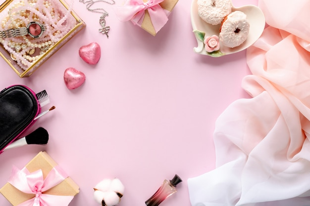 Area di lavoro fashion blogger con laptop e accessori femminili, prodotti cosmetici sul tavolo rosa.