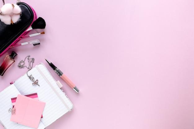 Area di lavoro fashion blogger con laptop e accessorio femminile, prodotti cosmetici sul tavolo rosa pallido.