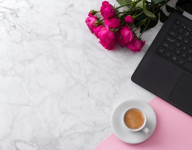 Area di lavoro femminile con computer portatile, bouquet di rose e caffè su un tavolo di marmo.