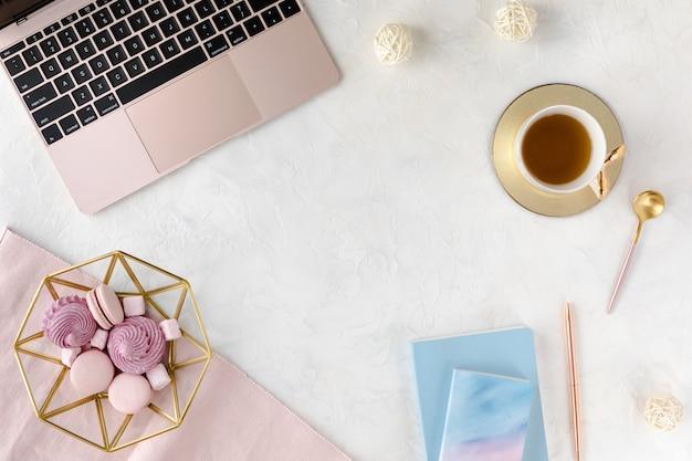 Area di lavoro femminile con laptop, tazza di tisana e dessert.