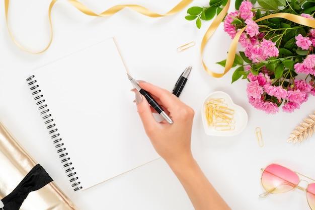 Area di lavoro femminile con taccuino di carta bianca e mano di donna che tiene la penna, fiori rosa rosa, accessori dorati, occhiali da sole