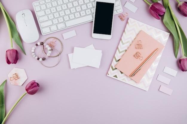 Area di lavoro femminile per scrivania con tulipani, laptop, occhiali, diario e clip dorate su viola