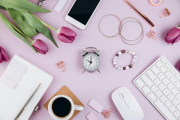 Area di lavoro femminile per scrivania con tulipani, tastiera, occhiali, clip dorate su viola
