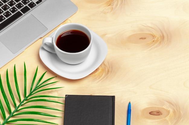 Area di lavoro in ufficio, scrivania in legno con laptop e tazza di caffè vista dall'alto