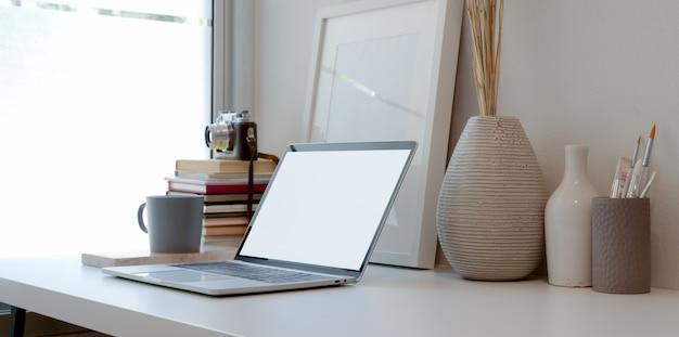 Area di lavoro minima con computer portatile a schermo vuoto, libri, vaso in ceramica