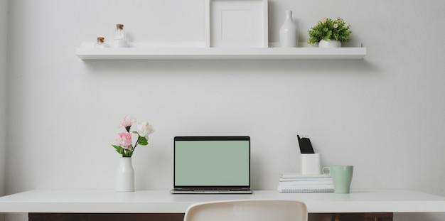 Area di lavoro minima con computer portatile aperto e decorazioni sullo scaffale