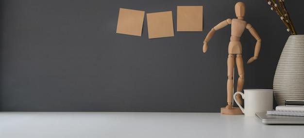 Area di lavoro minima con copia spazio e decorazioni sul tavolo bianco e parete grigio scuro