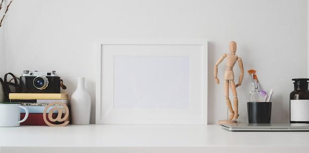 Area di lavoro minima con cornice per foto in bianco e articoli per ufficio sulla tavola di legno bianca e sulla parete bianca