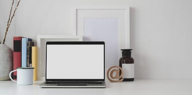 Area di lavoro minima con il computer portatile aperto dello schermo in bianco con gli articoli per ufficio e lo spazio della copia