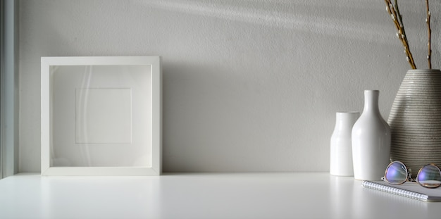 Area di lavoro minima con mock up frame e copia spazio sul tavolo bianco