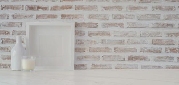 Area di lavoro minima con telaio e articoli per ufficio sul tavolo bianco con spazio di copia e muro di mattoni