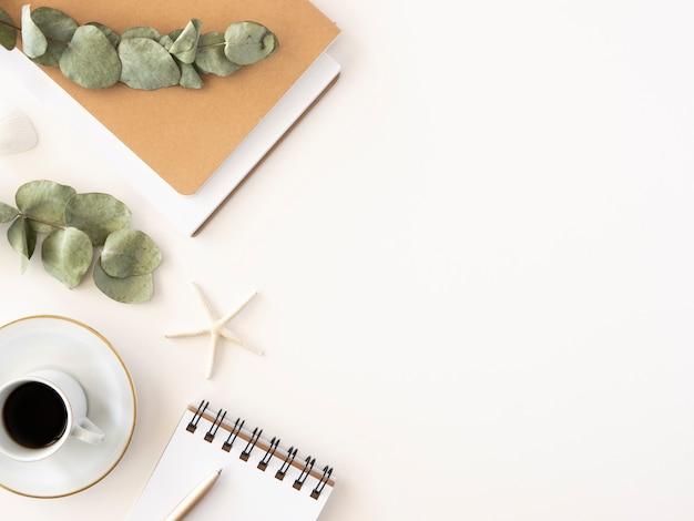 Area di lavoro minimale del blogger con taccuino, appunti, caffè e ramo di eucalipto