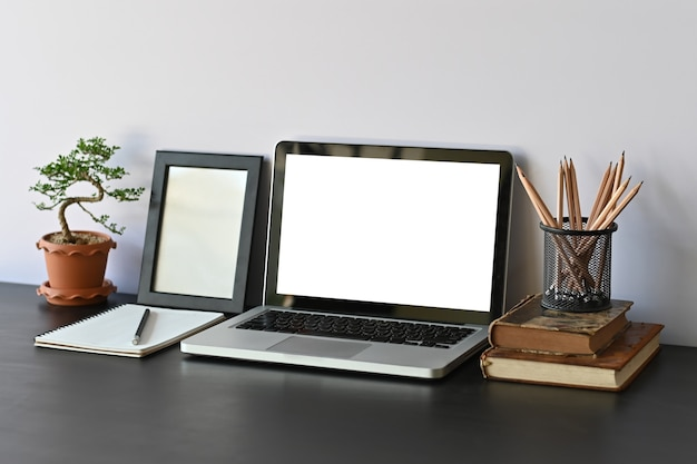 Area di lavoro mockup portatile e libri, matita, cornice per foto e bonsai sulla scrivania.