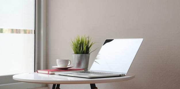 Area di lavoro moderna con il computer portatile e le decorazioni sulla tavola bianca