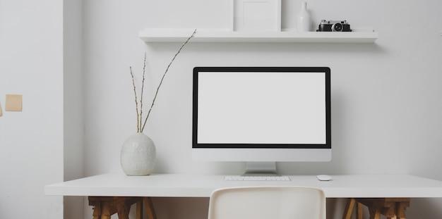 Area di lavoro moderna con il desktop computer dello schermo in bianco e le decorazioni sulla tavola bianca e sulla parete bianca
