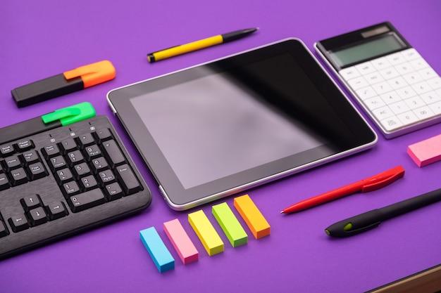 Area di lavoro moderna con tablet, tastiera e calcolatrice su sfondo viola. concetto piatto laico