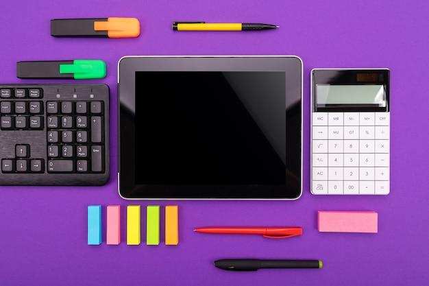 Area di lavoro moderna con tablet, tastiera e calcolatrice sulla porpora.