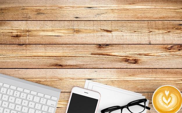 Area di lavoro moderna con tazza di caffè, carta, taccuino, tablet o smartphone e tastiera su legno