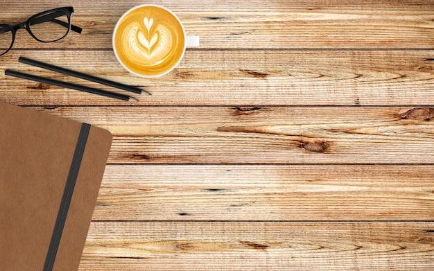 Area di lavoro moderna con tazza di caffè, taccuino e tastiera su legno