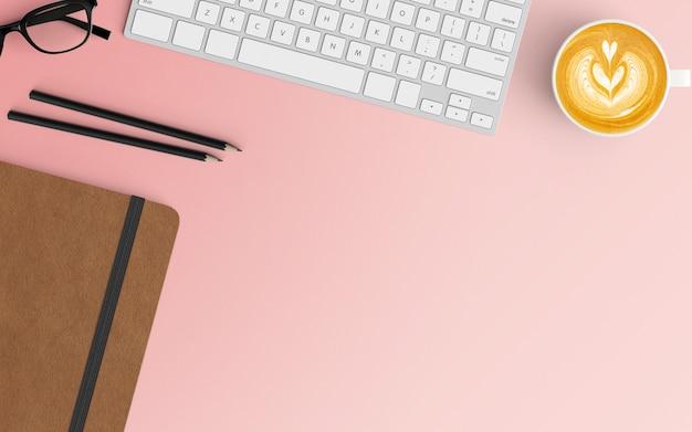 Area di lavoro moderna con tazza di caffè, tastiera e taccuino su colore rosa