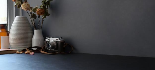 Area di lavoro moderna scura con copia spazio e fotocamera sulla scrivania nera e parete grigio scuro