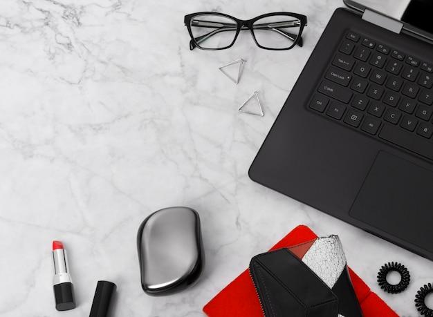 Area di lavoro piatta con laptop, agenda, occhiali, telefono cellulare, orecchini, cravatta, pettine e rossetto. elegante scrivania in marmo per ufficio.