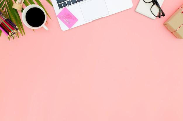 Area di lavoro piatta laici ufficio con computer portatile in bianco, vista superiore del computer portatile sfondo e lo spazio della copia su sfondo rosa