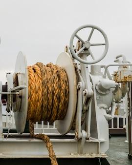 Argano con la corda arancio su un traghetto, backgrond nuvoloso bianco