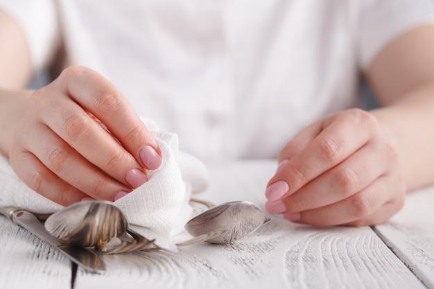 Argenteria chiazzata di pulizia femminile della mano con un prodotto di pulizia e un panno, cucchiaio d'argento di pulizia della mano della donna da vicino, argento lucidato