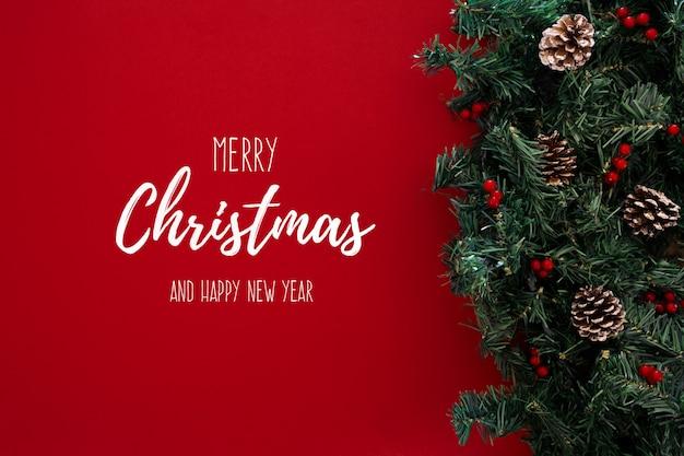 Argomento di buon natale su uno sfondo rosso con albero di natale