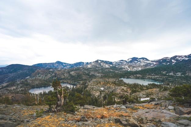 Ariel ha sparato delle scogliere e delle montagne con gli alberi che crescono intorno a loro vicino al lago tahoe, ca.