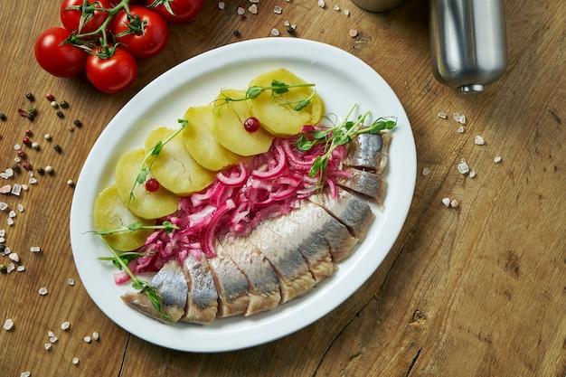 Aringhe norvegesi leggermente salate con patate al forno, pomodori e sottaceti su un piatto bianco. antipasti ucraini classici. vista dall'alto cibo su superficie di legno