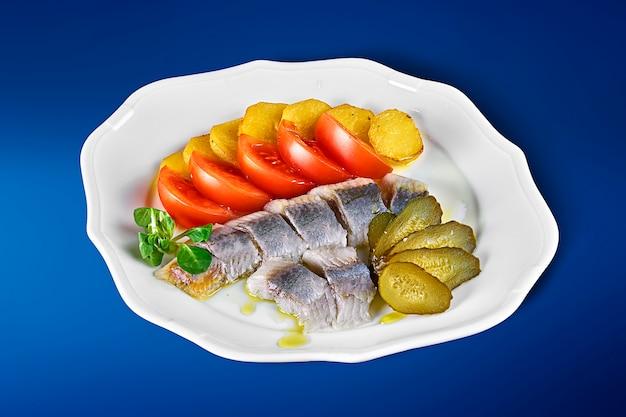 Aringhe norvegesi leggermente salate con patate al forno, pomodori e sottaceti su un piatto bianco. antipasti ucraini classici.