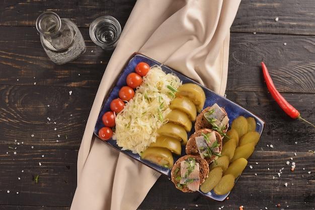 Aringhe salate con verdure in salamoia. su un tavolo di legno