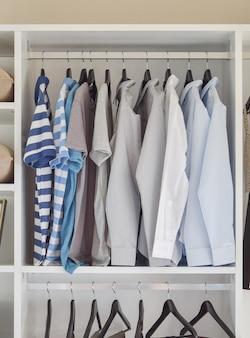Armadio moderno con fila di camicie appese nel guardaroba bianco