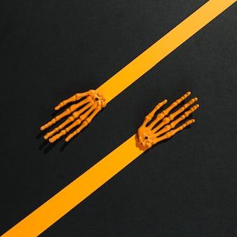 Armi arancioni di scheletro fatte di carta e ossa
