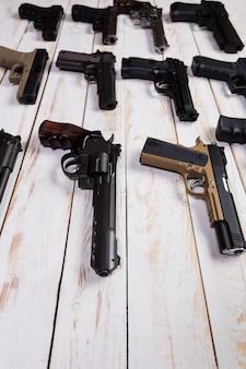 Armi da fuoco. pistola. il primo piano la pistola si trova su un fondo bianco di legno.