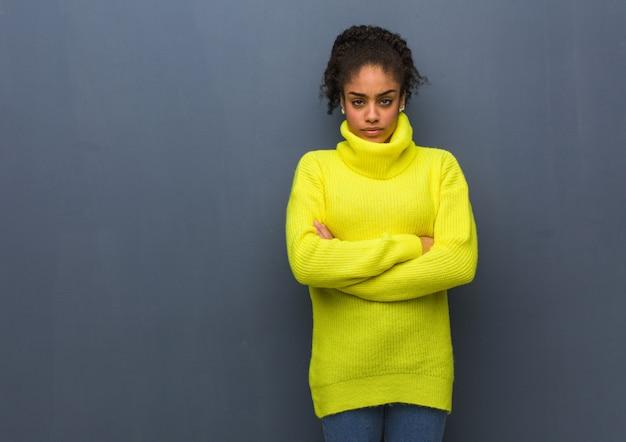 Armi dell'incrocio della giovane donna di colore rilassate