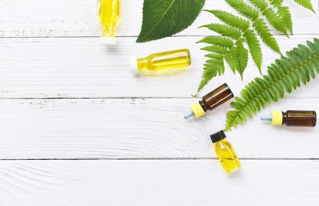 Aromaterapia aroma di bottiglie di olio alle erbe con formulazioni a base di erbe di foglie tra cui fiori di campo ed erbe su legno vista dall'alto, oli essenziali naturali su legno e foglie verdi