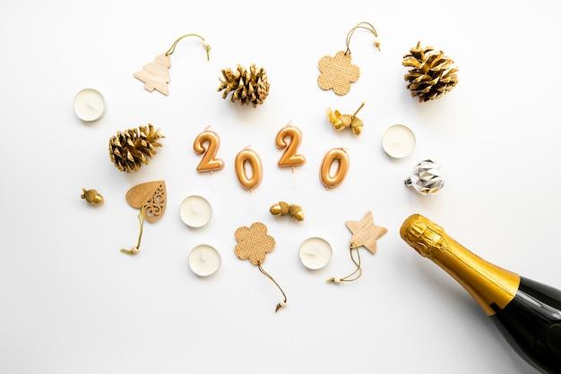 Arrangiamento di decorazioni e champagne con cifre del nuovo anno 2020