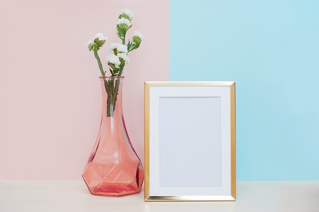Arredamento moderno con cornice in oro bianco, vaso e pianta tropicale su backgr blu rosa