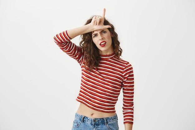 Arrogante donna sicura di sé che mostra il gesto perdente sulla fronte, deridendo la squadra persa