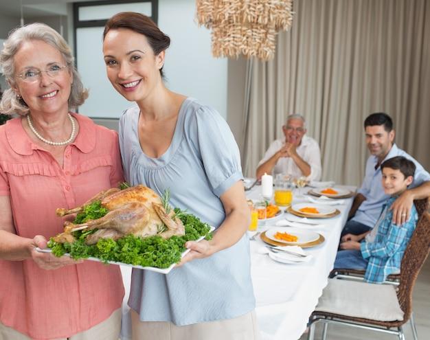 Arrosto di pollo della holding della nonna e della donna con la famiglia al tavolo da pranzo